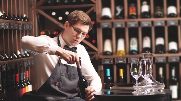 Elegante sumiller con pajarita descorcha una botella de vino en una tienda de vinos