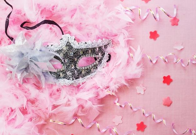Elegante superficie rosa con máscara plateada