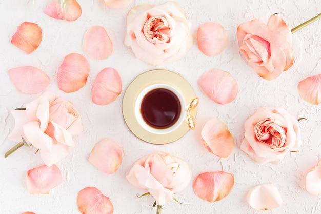 Elegante taza de café con rosas rosas, flores y pétalos