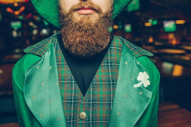 Elegante y tranquilo joven en pub. lleva traje verde de san patricio. guy tiene barba roja.