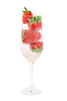 Elegante vaso lleno de agua mineral con burbujas de gas y jugosas fresas frescas naturales