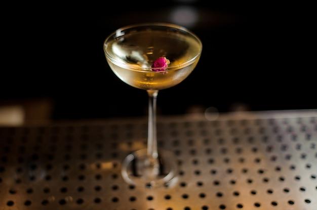 Elegante vaso lleno de sabroso cóctel dulce decorado con capullo de rosa rosa en la barra del bar