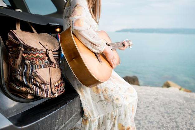 Elegante viajero tocando la guitarra acústica