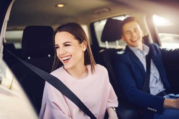Elegantemente vestida, sonriente morena caucásica conduciendo en coche y mirando por la ventana mientras su novio conducía.