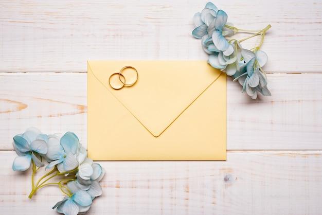 Elegantes anillos de boda en la mesa con flores.