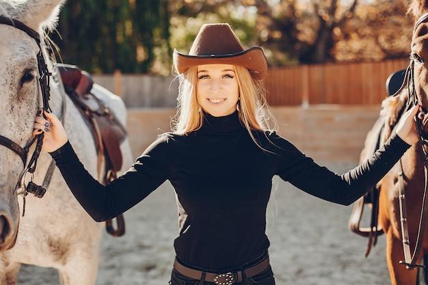 Elegantes chica con un caballo en un rancho.