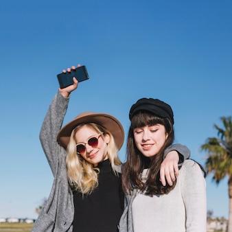 Elegantes chicas modernas posando felizmente en la calle