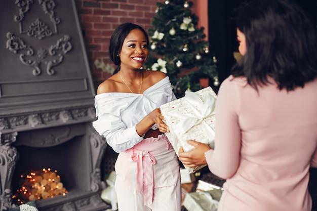 Elegantes chicas negras en las decoraciones navideñas