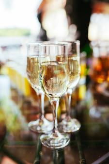 Elegantes copas con champán de pie en una fila en la mesa de servicio durante una fiesta o celebración