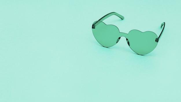 Elegantes gafas en forma de corazón sobre fondo de papel con espacio de copia. hermosas gafas de sol turquesa de moda. concepto de moda de verano.