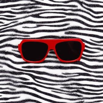 Elegantes gafas de sol rojas y estampado animal de cebra. estado de ánimo de safari