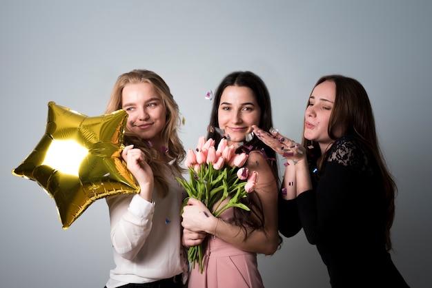 Elegantes hembras alegres divirtiéndose en la fiesta