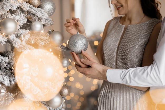 Elegantes hombres y mujeres vestidos con bata plateada se abrazan tiernamente de pie ante un árbol de navidad