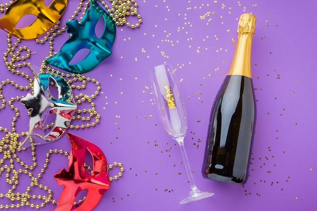 Elegantes máscaras de carnaval con botella de champagne