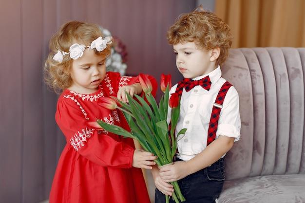 Elegantes niños pequeños con ramo de tulipanes