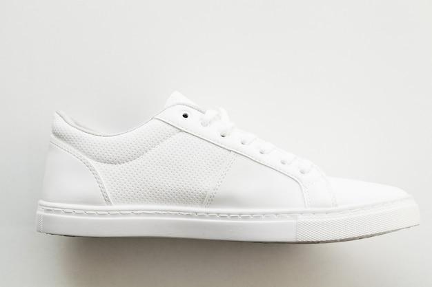 Elegantes zapatillas de moda blancas sobre blanco.