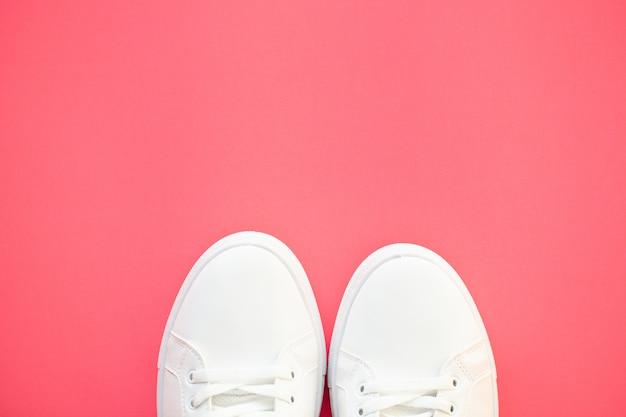 Elegantes zapatillas de moda blancas sobre rosa.