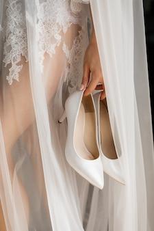 Elegantes zapatos de boda blancos en la mano de la novia