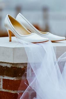 Elegantes zapatos nupciales y blancos en la playa.