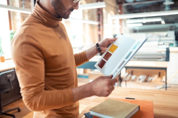 Elegir color. cerca del escritor barbudo vistiendo cuello polo naranja eligiendo el color de la portada del libro