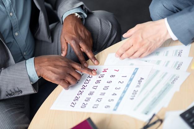Elegir fecha. hombre de negocios de piel oscura que elige la fecha para la próxima negociación con el socio