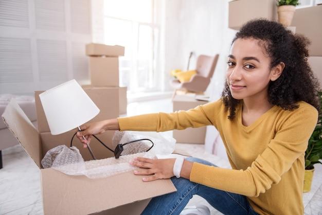Elemento importante. encantadora niña de pelo rizado sonriendo a la cámara y sacando una lámpara de la caja mientras desempaca sus pertenencias en un piso nuevo