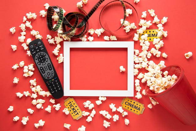Elementos de cine y marco blanco sobre fondo rojo