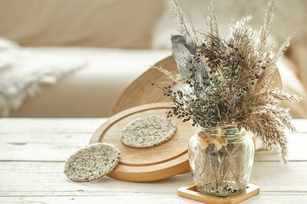 Elementos decorativos en el acogedor interior de la habitación, un jarrón con flores secas sobre una mesa de madera clara.