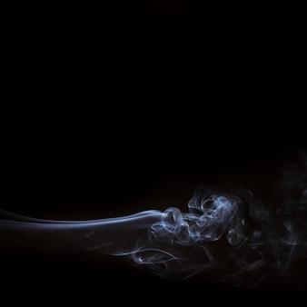 Elementos de humo blanco sobre fondo negro con espacio de copia para escribir el texto