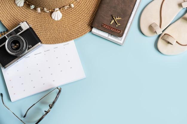 Elementos de viaje y calendario sobre fondo de color con espacio de copia, concepto de planificación de vacaciones
