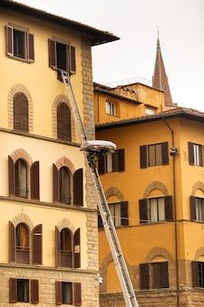 Elevación de la carga al último piso mediante una gran escalera en el centro de florencia, italia, toscana.