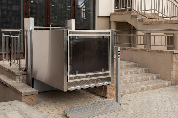 Elevador de escalera de metal de última generación, elevador de plataforma, elevador de personas discapacitadas fuera del edificio de apartamentos, vista de ángulo bajo