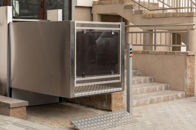 Elevador de escaleras, elevador de plataforma, elevador de personas discapacitadas cerca de las modernas instalaciones de apartamentos, vista diagonal