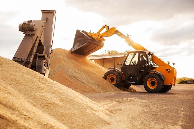 Elevador de granos. finca agraria de paisaje rural. granos tractormakes volcar silos