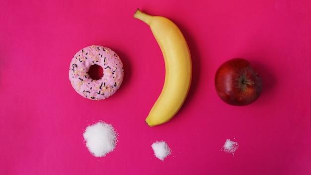 Elija frutas saludables en lugar de dulces poco saludables con gran cantidad de azúcar - fondo rosa