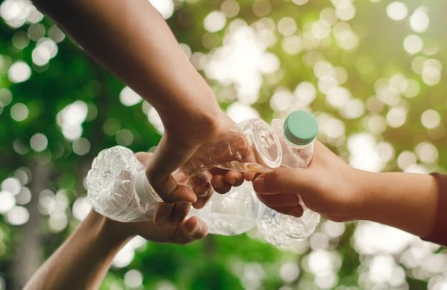 Eliminando residuos para conservar un mundo mejor con buen medio ambiente y atmósfera natural de la mano en equipo, unidad, sosteniendo botellas de plástico juntas. reducir el calentamiento global salvar el mundo