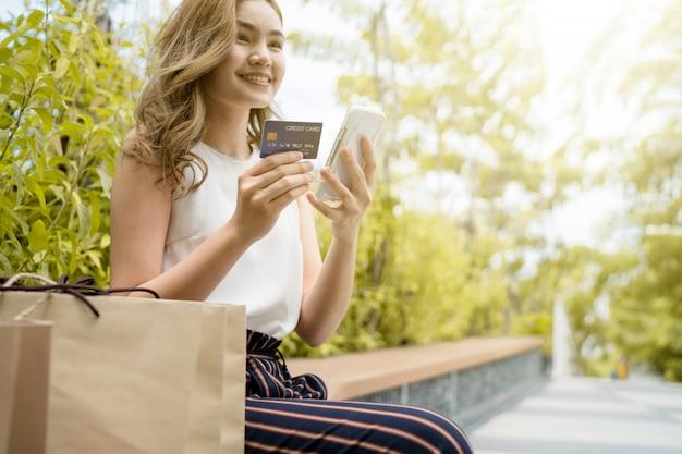 Ella compra en el centro comercial y usa un teléfono móvil para comunicarse con amigos y usa bolsas de papel para comprar.
