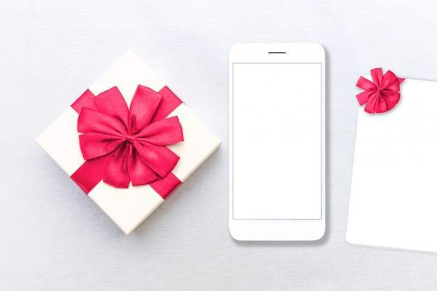 Embalaje caja de paquetes rojo con etiqueta y teléfono móvil.