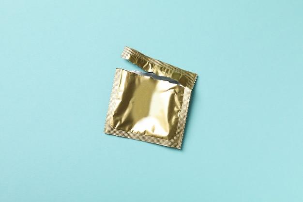 Embalaje de condón en blanco vacío sobre superficie azul