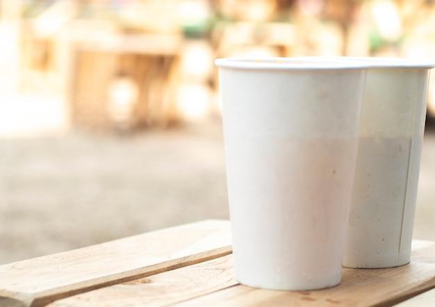 Embalaje ecológico maqueta de vidrio de papel desechable para café. té . jugo y agua. listo para el diseño en la mesa de madera. fondo de tono vintage. guardar la idea del concepto de medio ambiente.