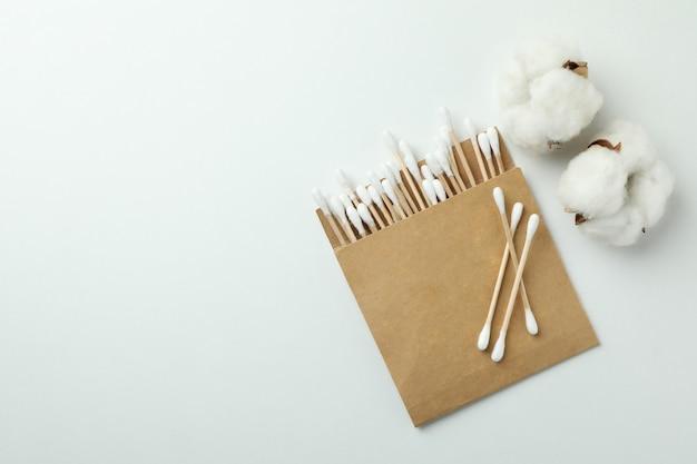 Embalaje con hisopos de algodón y algodón sobre fondo blanco.