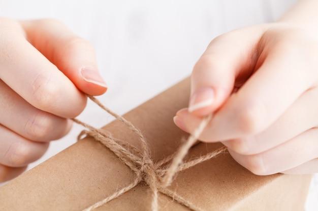 Embalaje de regalo hecho a mano en papel artesanal por mujer