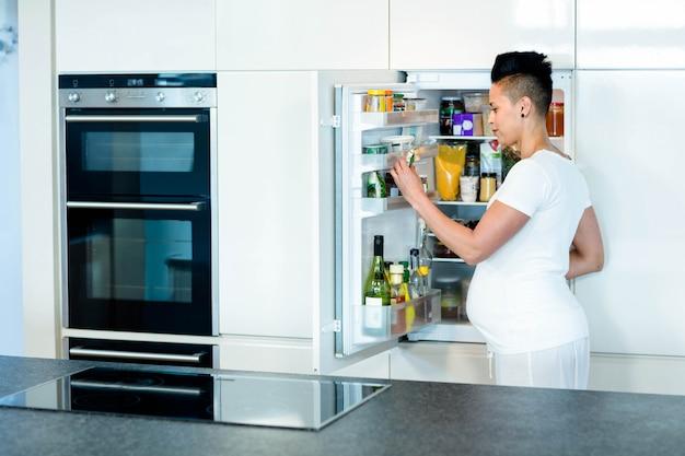 Embarazada tocando su vientre mientras busca comida en la nevera