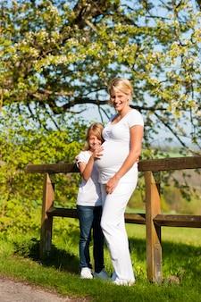Embarazo - niña tocando el vientre de la madre embarazada