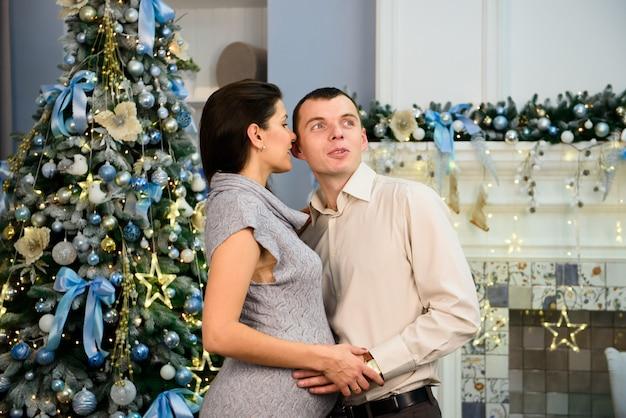 Embarazo, vacaciones de invierno y concepto de la gente - esposa embarazada feliz con el marido en casa en la navidad. familia joven celebrando la navidad en casa.