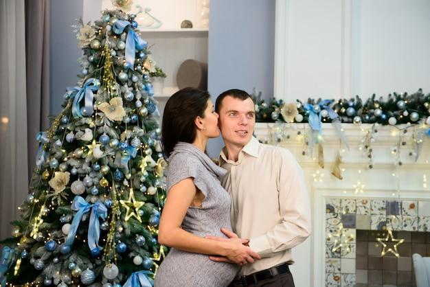 Embarazo, vacaciones de invierno y concepto de la gente - esposa embarazada feliz con el marido en casa en la navidad.