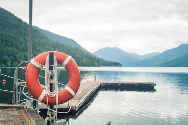 Embarcadero de madera con anillo de vida rojo en el lago de montaña