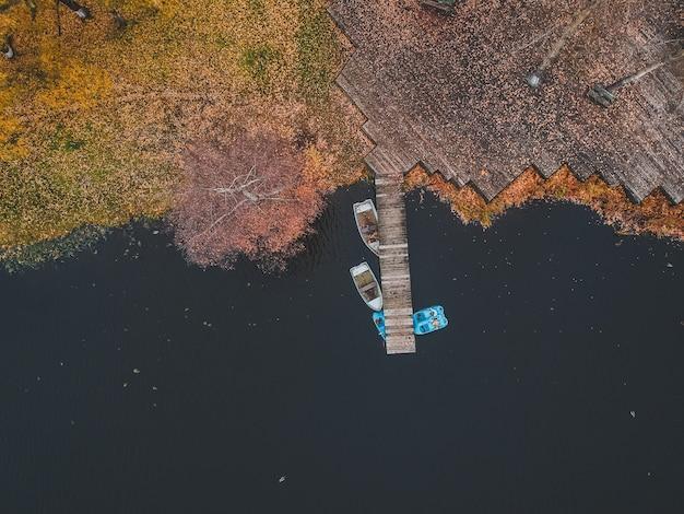 Embarcadero de la vista aérea con los barcos de madera en la orilla de un lago pintoresco, bosque del otoño. san petersburgo, rusia.