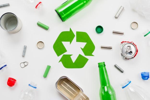 Emblema de reciclaje alrededor de diferentes basuras.