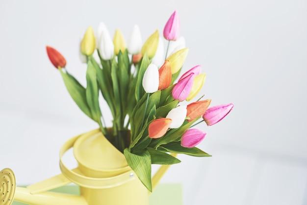 Embudo amarillo con tulipanes de pequeñas flores de colores. hermosas flores de primavera
